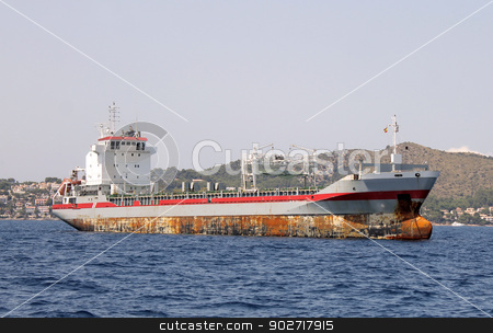 Rusty cargo ship at sea stock photo, Side view of rusty cargo ship at sea with coastline of Spain in background. by Martin Crowdy