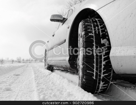 Winter tyre stock photo, Close up of a cars tires on a snowy road by Nneirda