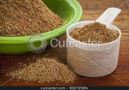 noni fruit powder  stock photo, measuring scoop of noni fruit powder with a bowl on wooden surface by Marek Uliasz