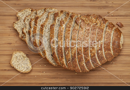 sliced loaf of bread stock photo, a small sliced loaf of bread with whole wheat grain and seeds on bamboo cutting board by Marek Uliasz
