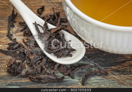 oolong black tea stock photo, a cup of oolong black tea with loose leaf and teaspoon by Marek Uliasz