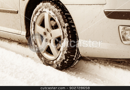 Winter tyre stock photo, Close up of a cars tires on a snowy road - sepia tone by Nneirda
