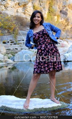 Young Hispanic Woman stock photo, Young Hispanic woman near a creek. by Henrik Lehnerer