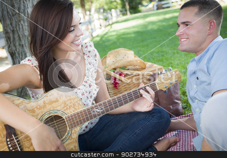 Mixed Race Couple at the Park Playing Guitar and Singing stock photo, Happy Mixed Race Couple at the Park Playing Guitar and Singing Songs. by Andy Dean