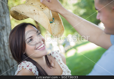 Mixed Race Romantic Couple with Cowboy Hat Flirting in Park stock photo, Happy Mixed Race Romantic Couple with Cowboy Hat Flirting in the Park. by Andy Dean
