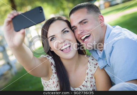 Mixed Race Couple Taking Self Portrait in Park stock photo, Happy Mixed Race Couple Taking Self Portrait with A Smart Phone in the Park. by Andy Dean