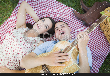 Mixed Race Couple at the Park Playing Guitar and Singing stock photo, Happy Mixed Race Couple On Picnic Blanket at the Park Playing Guitar and Singing Songs. by Andy Dean