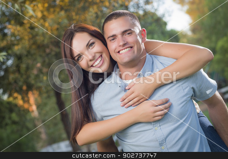 Mixed Race Romantic Couple Portrait in the Park stock photo, Happy Mixed Race Romantic Couple Piggyback Portrait in the Park. by Andy Dean