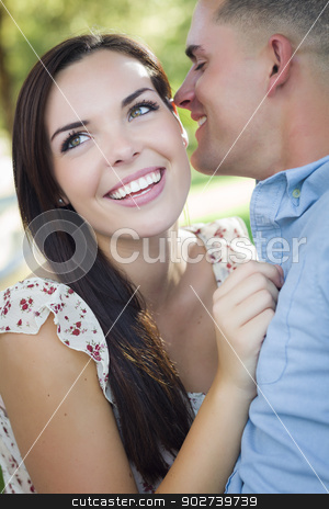 Mixed Race Romantic Couple Whispering in the Park stock photo, Happy Mixed Race Romantic Couple Whispering in the Park. by Andy Dean