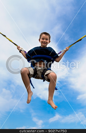 Young boy swinging high in the air stock photo, Young boy swinging high in the air against a cloudy blue summer sky in a harness attached to cables or ropes with a beaming smile of enjoyment by Ozgur Coskun