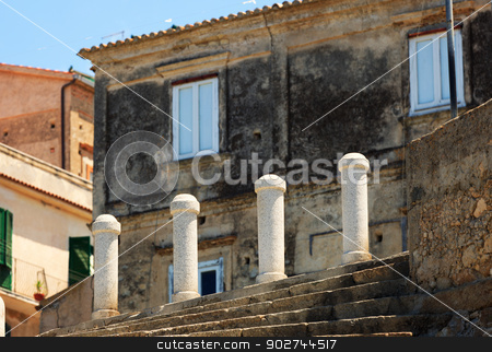 Architectural detail in Tropea stock photo, Small columns protecting pedestrian footsteps from trafficway against grungy building in Tropea, Calabria by Natalia Macheda