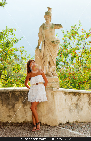 Woman and statue of warrior stock photo, Beautiful young woman looking at the statue of antique warrior with a smile by Natalia Macheda