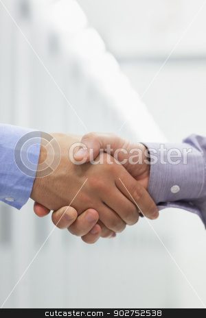 People shaking hands stock photo, Two men shaking hands in hallway of data center by Wavebreak Media