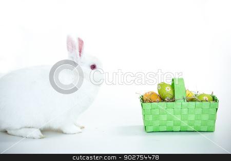 White bunny facing basket of easter eggs stock photo, White bunny facing wicker basket of easter eggs on white background by Wavebreak Media
