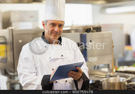 Chef using his digital tablet and looking at camera stock photo, Chef using his digital tablet and looking at camera in the kitchen by Wavebreak Media