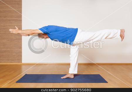 yoga man stock photo, An image of a man doing yoga exercises - Virabhadrasana by Markus Gann