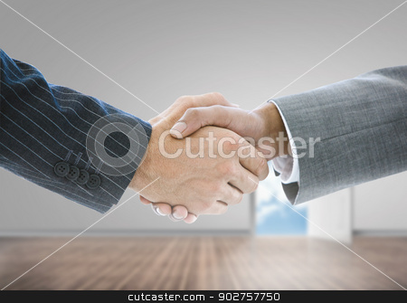Close up of businessmen shaking hands stock photo, Close up of businessmen shaking hands in a grey room by Wavebreak Media