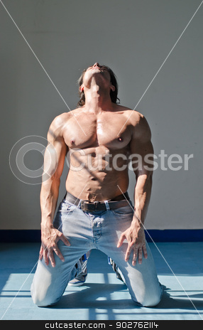 Attractive young man with muscular body, kneeling and looking up stock photo, Handsome young muscle man shirtless kneeling on the floor, holding head up, wearing jeans by Stefano Cavoretto