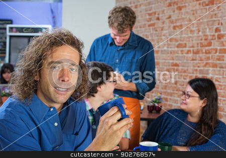 Cheerful Man with Mug stock photo, Cheerful young man holding coffee mug in cafe by Scott Griessel