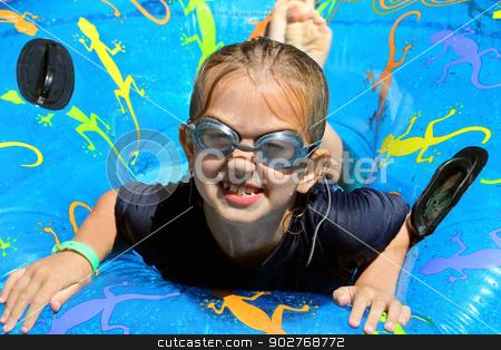 Girl playing in swimming pool stock photo, Cute girl playing on inflatable in swimming pool. by Martin Crowdy