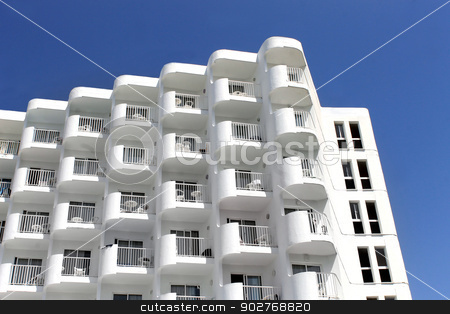 White hotel building stock photo, Low angle view of old white hotel building with blue sky background. by Martin Crowdy