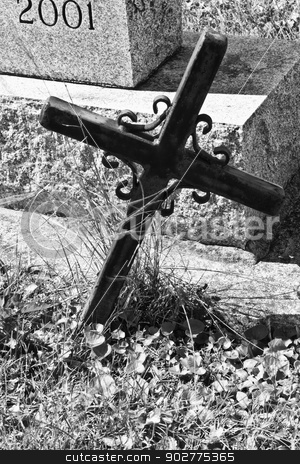 Small Cemetery Cross stock photo, A Small Cross Set in Front of a Tombstone in a Cemetery by jetcityimage