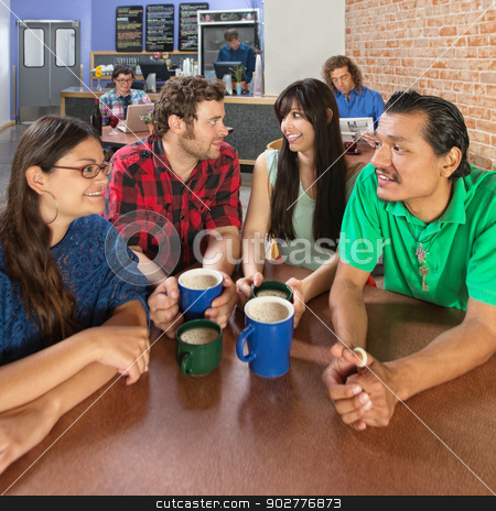 Four Happy People Talking stock photo, Wide angle view of four people talking in a coffee house by Scott Griessel