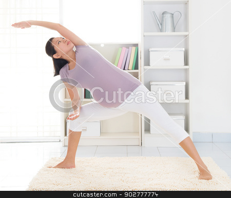 Maternal yoga at home stock photo, Prenatal health concept. Full length healthy 8 months pregnant calm Asian woman meditating or doing yoga exercise at home. Relaxation yoga side stretching pose. by szefei
