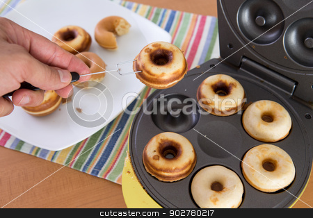 Baking Mini Donuts stock photo, Clean hands baking mini donuts in the donut making machine by Ozgur Coskun