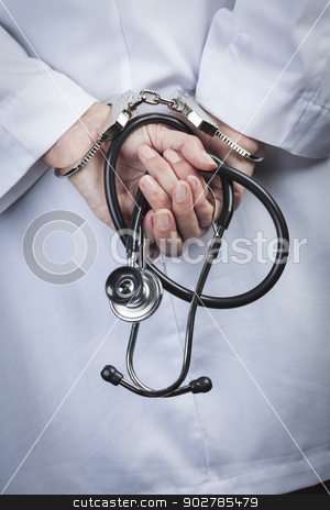 Female Doctor or Nurse In Handcuffs Holding Stethoscope stock photo, Female Doctor or Nurse In Handcuffs and Lab Coat Holding Stethoscope. by Andy Dean
