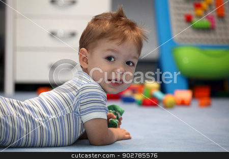 A happy baby boy lying on a floor stock photo, A happy baby boy lying on a floor in children's room by vladacanon1