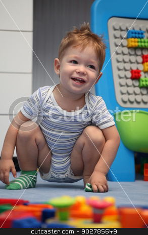 A happy baby boy on a floor stock photo, A happy baby boy on a floor in children's room by vladacanon1