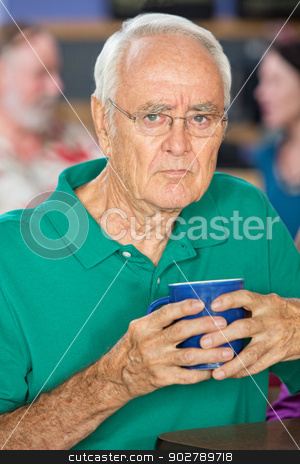 Sulky Older Man stock photo, Sulky senior male holding coffee mug in cafe by Scott Griessel