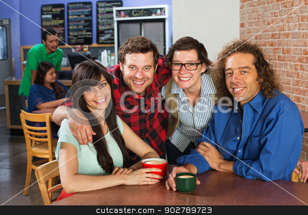 Friends Embracing stock photo, Four smiling friends embracing in a coffee house by Scott Griessel