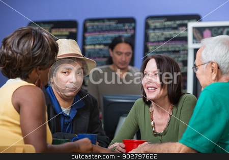 Happy Woman Listening to Friends stock photo, Happy adult woman listening to friends in restaurant by Scott Griessel