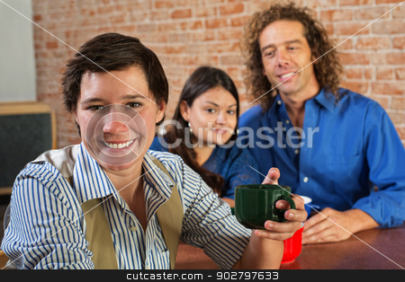 Woman Holding Coffee Mug stock photo, Smiling Caucasian woman holding coffee mug with friends by Scott Griessel
