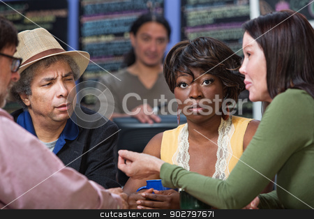 Perplexed Woman with Group in Cafe stock photo, Perplexed woman in diverse group in restaurant by Scott Griessel