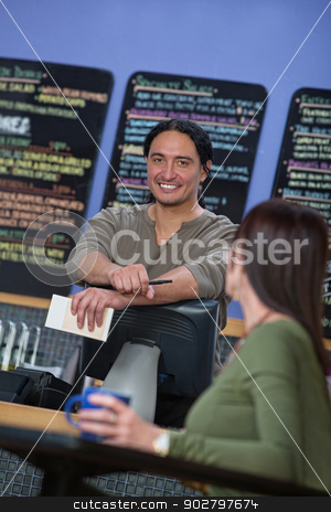 Handsome Cafe Waiter stock photo, Handsome cafe owner behind counter with customer by Scott Griessel