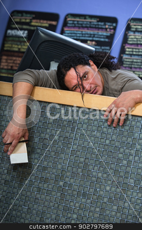 Bored Cafe Owner stock photo, Bored male restaurant owner at counter with receipt book by Scott Griessel