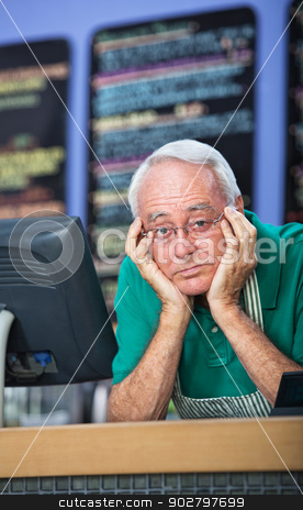 Sad Man in Cafe stock photo, Sad man with apron behind restaurant counter by Scott Griessel