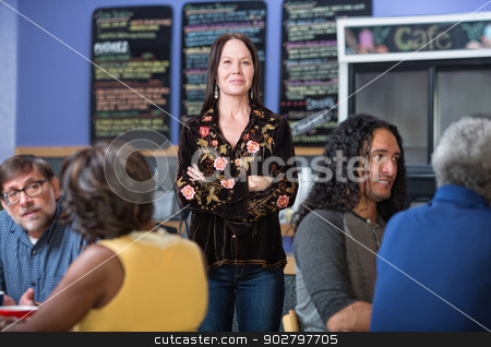 Pretty Woman in Cafe stock photo, Cheerful woman standing in group of customers in cafe by Scott Griessel