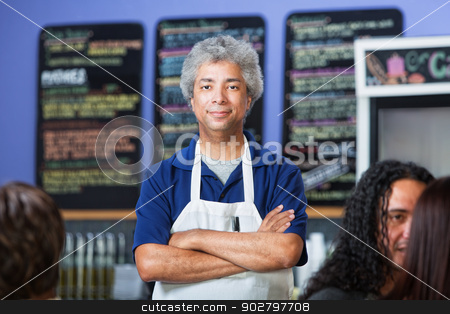 Confident Cafe Owner stock photo, Man with folded arms standing in a coffee house by Scott Griessel