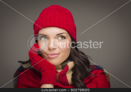 Smiling Mixed Race Woman Wearing Mittens Looks to Side stock photo, Happy Mixed Race Woman Wearing Winter Hat and Gloves Looking to the Side on Gray Background. by Andy Dean