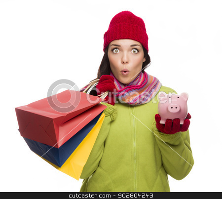 Concerned Expressive Mixed Race Woman Holding Shopping Bags and  stock photo, Concerned Expressive Mixed Race Woman Wearing Winter Clothes Holding Shopping Bags and Piggybank Isolated on White Background. by Andy Dean