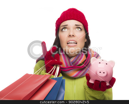 Stressed Mixed Race Woman Holding Shopping Bags and Piggybank stock photo, Stressed Mixed Race Woman Wearing Winter Clothing Looking Up Holding Shopping Bags and Piggybank Isolated on White Background. by Andy Dean