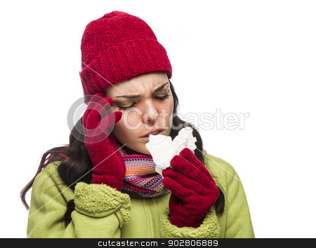 Sick Mixed Race Woman Blowing Her Sore Nose with Tissue stock photo, Sick Mixed Race Woman Wearing Winter Hat and Gloves Blowing Her Sore Nose with a Tissue Isolated on White Background.  by Andy Dean