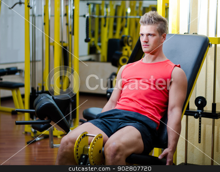 Handsome young man working out on gym equipment stock photo, Attractive and fit young man in gym working out legs and exercising on equipment by Stefano Cavoretto