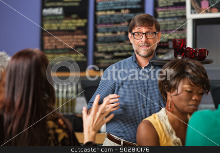 Man Serving Drinks stock photo, Customer signalling waiter with drinks on trays by Scott Griessel