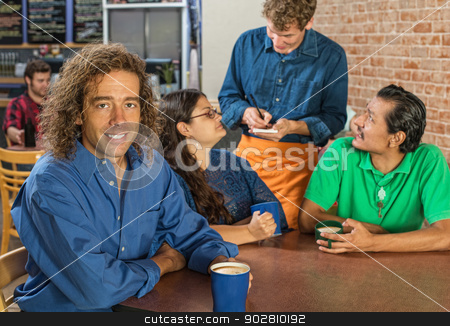 Man with Friends and Barista stock photo, Grinning man with friends and barista at cafe by Scott Griessel