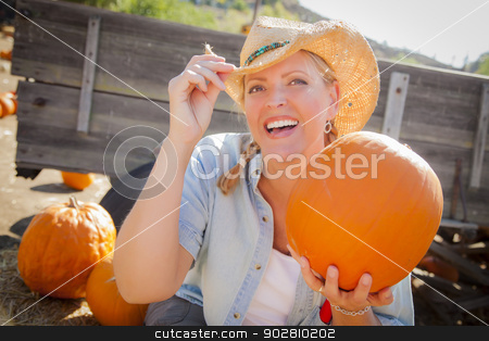 Beautiful Blond Female Rancher Wearing Cowboy Hat Holds a Pumpki stock photo, Beautiful Blond Female Rancher Wearing Cowboy Hat Holds a Pumpkin in a Rustic Country Setting.  by Andy Dean